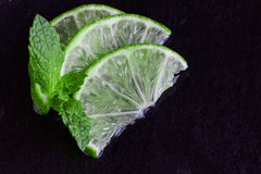 Lime slices and mint on slate background Royalty Free Stock Images