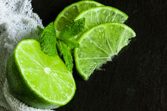 Lime, slices and mint with white cloth on slate background Stock Image