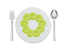 Lime slices on plate, spoon and fork isolated on white Stock Image