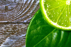 Lime slices 3. Slice of lime with leaves on a piece of wood Royalty Free Stock Photo
