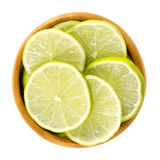 Lime slices in wooden bowl over white Stock Photo