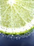 Lime in sparkling water. On blue background Stock Images
