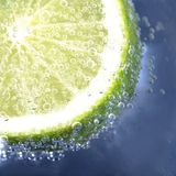 Lime in sparkling water. On blue background Stock Photo