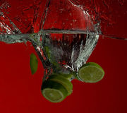 Lime splash. Lime with water splash on red Stock Images