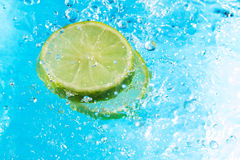 Lime splash in water, top view. Bubbles with fruit reflection Royalty Free Stock Photos