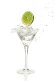 Lime splashing into a cocktail. Green lime splashing into a martini glass Royalty Free Stock Images