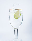 Lime splashing into glass of water Royalty Free Stock Image