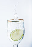 Lime splashing into glass of water Stock Photography