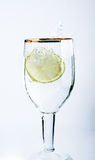 Lime splashing into glass of water Stock Image