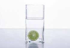 Lime splashing into glass of water on white background. And Royalty Free Stock Photos