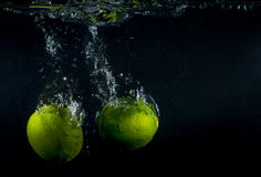 Lime splashing in water on black Stock Image