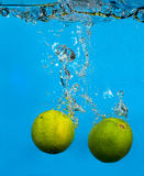Lime splashing in water on blue Royalty Free Stock Image
