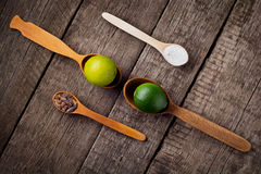 Lime on spoons with salt and sugar spoon on the kitchen table. Royalty Free Stock Photography