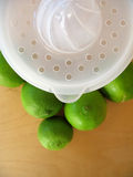 Lime Squeeze 2. A fruit squeezer with fresh green limes. Focused at the fruit squeezer stock photo