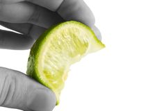 Lime squeeze. A close up on a fresh lime wedge being squeezed isolated on a white background Stock Photography
