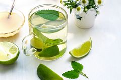 Lime tea with mint in a glass cup, honey and chamomile. On a white background stock image