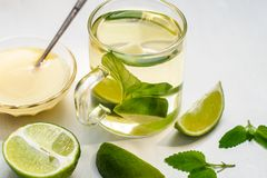 Lime tea with mint in a glass cup and honey. On a white background royalty free stock image