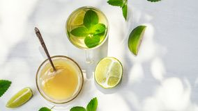 Lime tea with mint in a glass cup and honey on a white background. With sunbeams royalty free stock photography