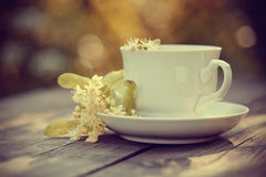 Lime tea in a white cup. On a wooden table royalty free stock photo