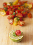 Lime, tomato and cilantro in front. A lime, tomato and cilantro sprig stacked in front of a group of chopped yellow and red tomatoes, cilantro sprinkled with stock images