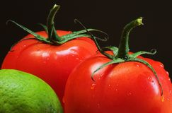 Lime and tomatoes. Two red tomatoes and part of a lime macro image Royalty Free Stock Photos