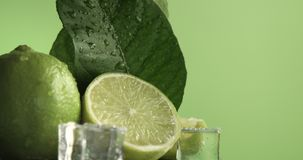 Lime turning on it`s axis on green background covered by water drops with ice cubes. Lime turning on it`s axis on green background covered by water drops stock footage