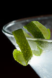 Lime twist garnish. Lime twist on the rim of a martini glass used as a garnish isolated on a black background royalty free stock photo
