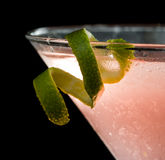 Lime twist garnish. Lime twist on the rim of a martini glass used as a garnish isolated on a black background stock images