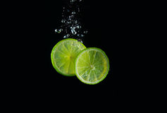 Lime in water. Two pieces of fresh juicy lime making bubbles in water Royalty Free Stock Images