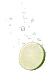 Lime in water with air bubbles. Lime falling into water, with air bubbles, in front of white background, union of the three things essential to live which is air royalty free stock image