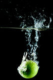 Lime Water Splash. Lime drop in a water tank creating a splash Royalty Free Stock Photos