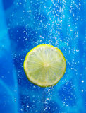 Lime in a water splash. A lime dropping ina splash of water drops Stock Photo