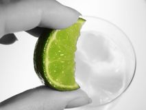 Lime wedge and cool drink. Hand squeezing lime wedge into cool drink Royalty Free Stock Photos