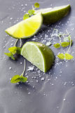 Lime Wedges with Sea Salt and Micro Herbs over Slate Stock Photo