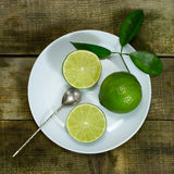 Lime in the white plate with old spoon. On wooden background royalty free stock photography
