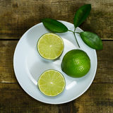Lime in the white plate. On wooden background royalty free stock images