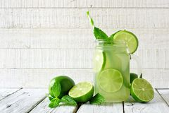 Limeade in a mason jar glass with a white wood background Royalty Free Stock Images