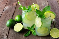 Limeade in mason jar glasses on rustic wood Royalty Free Stock Images