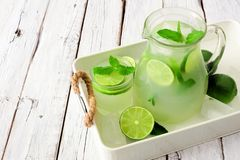 Limeade with pitcher and glass in serving tray against white wood Royalty Free Stock Image