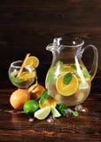 Limefrukt apelsin, mintkaramell - ingredienser för en fruktsaft på en tabellbakgrund En coctail med rom, starksprit och frukter k royaltyfri bild