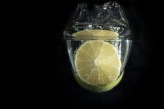 Limefrukt faller djupt under vatten Arkivbild
