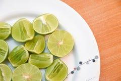 Limefrukt i den vita maträtten på träblackground royaltyfri foto