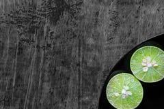 Limefrukt i svart maträtt på den wood tabellen Arkivfoto