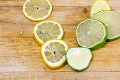 Limefrukt- och citronskivor på det wood brädet Arkivfoto