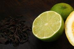 Limefrukt och te på en träbakgrund close upp arkivbilder
