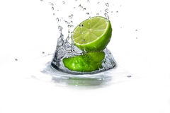 Limefrukt- och vattendroppe Arkivfoto