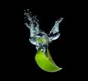 Limefrukt skivar att falla in i vatten royaltyfria bilder