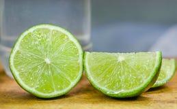 Limefrukt som skivas över träskärbräda med lemonadexponeringsglas i bakgrunden Royaltyfri Bild