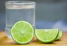 Limefrukt som skivas över träskärbräda med lemonadexponeringsglas i bakgrunden Arkivbild