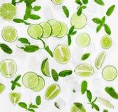 Limefrukter, ny mintkaramell och is för mojito på vit bakgrund Arkivfoto